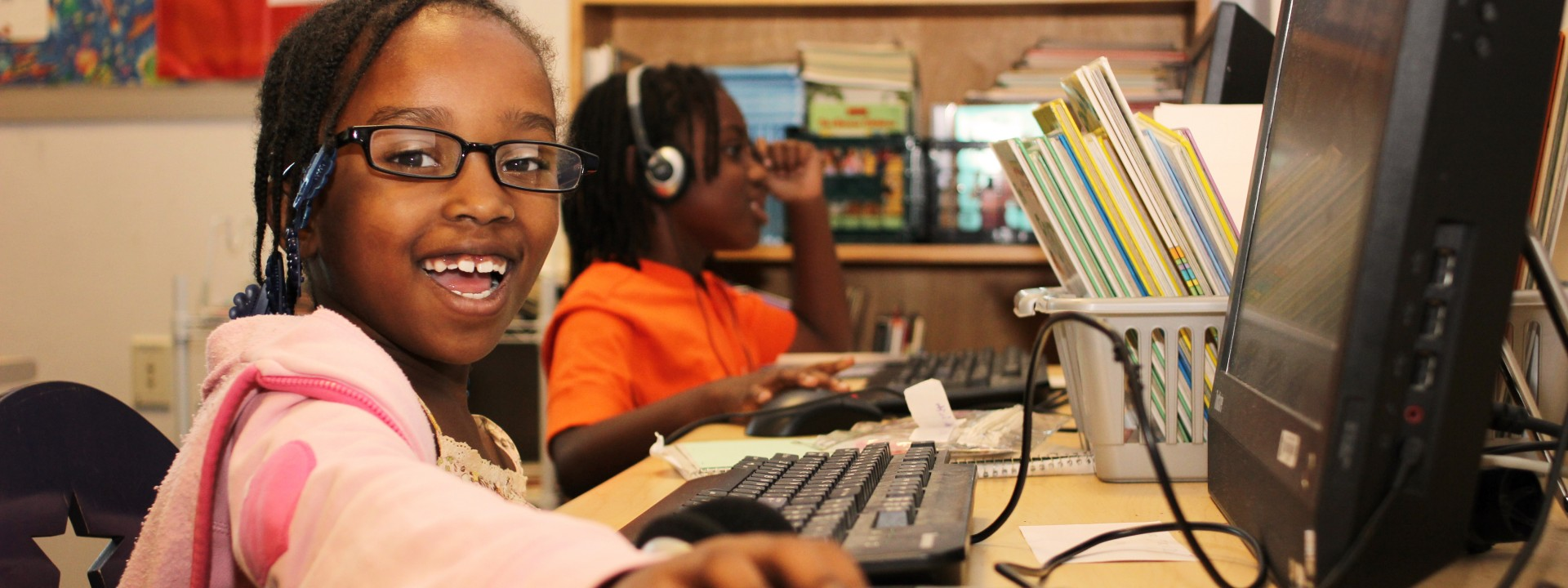Smiling children using computers at the Honickman Learning Center Comcast Technology Labs